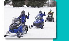 Three people driving snowmobiles waving